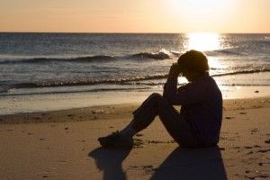 Image credit: <a href='http://www.123rf.com/photo_5902698_mature-woman-sits-on-the-beach-with-her-head-bowed-and-praying-as-the-sun-sets-on-the-water.html'>sframe / 123RF Stock Photo</a>