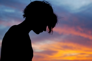 Silhouetted female in front of sunset sky